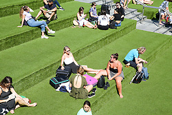 © Licensed to London News Pictures. 23/08/2019. London, UK. People enjoy the warm weather in Granary Square, King's Cross, London. According to the Met Office, the temperatures are forecast to increase to 30 degrees celsius for the bank holiday weekend.  Photo credit: Dinendra Haria/LNP