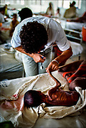 A doctor of the International Committee of the Red Cross examines a dying Ethiopian child ¾ part of the humanitarian work of the ICRC in an increasingly unstable world. The cause of the 1983-1985 famine is often ascribed to drought, but food shortages were the byproduct of an anti-government insurgency and the equally deadly government campaign against the rebels.  © Steve Raymer / National Geographic Creative