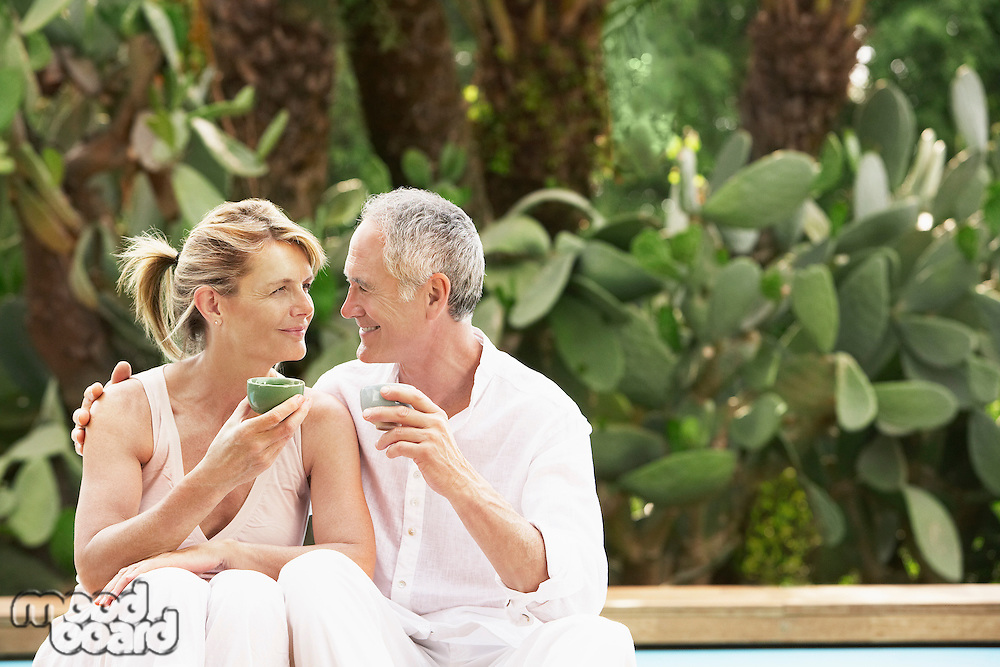 Middle-aged couple sitting by pool drinking tea