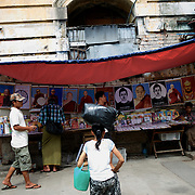 May 18, 2013 - Yangon, Myanmar: Locals pass by a street stall selling religious portraits in central Yangon. (Paulo Nunes dos Santos/Polaris)