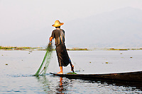 Fisherman standing in canoe gathering fishing net, Inle Lake, Myanmar. People and places fine art photography prints, stock images.