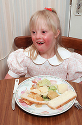 Portrait of young girl with Downs syndrome eating meal at table,