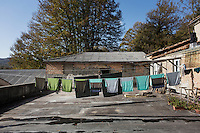 """SOVERIA MANNELLI, ITALY - 17 NOVEMBER 2016: Woolen clothing items are dried on the rooftop of the Lanificio Leo woolen mill here in Soveria Mannelli, Italy, on November 17th 2016.<br /> <br /> Lanificio Leo was the first and last machine-operated woolen mill of Calabria, founded in 1873, it employed 50 people until the 1970s, when national policies to develop Italy's South cut out small businesses and encouraged larger productions or employment in the public administration.<br /> <br /> The woolen mill was on stand-by for about two decades, until Emilio Salvatore Leo, 41, started inviting international designers and artists to summer residencies in Soveria Mannelli. With their inspiration, he tried to envision a future for his mill and his town that was not of a museum of the past,<br /> Over the years, Mr. Leo transformed his family's industrial converter of Calabrian wool into a brand that makes design products for home and wear. His century old machines now weave wool from Australia or New Zealand, cashmere from Nepal and cotton from Egypt or South America. He calls it a """"start-up on scrap metals,"""" referring to the dozens of different looms that his family acquired over the years.<br /> <br /> Soveria Mannelli is a mountain-top village in the southern region of Calabria that counts 3,070 inhabitants. The town was a strategic outpost until the 1970s, when the main artery road from Naples area to Italy's south-western tip, Reggio Calabria went through the town. But once the government started building a motorway miles away, it was cut out from the fastest communications and from the most ambitious plans to develop Italy's South. Instead of despairing, residents benefited of the geographical disadvantage to keep away the mafia infiltrations, and started creating solid businesses thanks to its administrative stability, its forward-thinking mayors and a vibrant entrepreneurship numbering a national, medium-sized publishing house, a leading school furniture manufacture"""