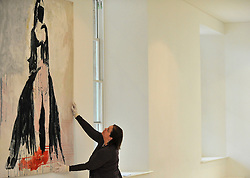"© under license to London News Pictures. LONDON, UK  05/05/2011. A gallery worker positions the tapestry 'The Black Cat' by Tracy Emin which took seven years to complete.  The unveiling today (5 May 2011) of Tracey Emin's first tapestry ahead of the launch of COLLECT, the Crafts Council's international craft fair for contemporary objects at the Saatchi Gallery, London. Tracy Emin say's: ""The Black Cat is one of my favourite paintings. It took me seven years to complete...""Photo credit should read Stephen Simpson/LNP."