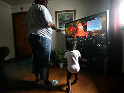 09 July 2006. New Orleans. Louisiana. <br /> Finding Faith. <br /> Faith Figueroa. A day in the life of. Faith's mother Miriam puts a DVD on the TV to keep Faith amused before her other children awake.<br /> Following a ten month search for the little girl whose face appeared on the Sept 19th, 2005 cover of Newsweek magazine, Faith's mother, Miriam Figueroa has returned to town with her three children. Faith, (1 yrs), Anfernya (5yrs) and Jacquelyn (13 yrs). <br /> Credit; Charlie Varley/varleypix.com