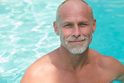 portrait of a handsome mature man in a swimming pool