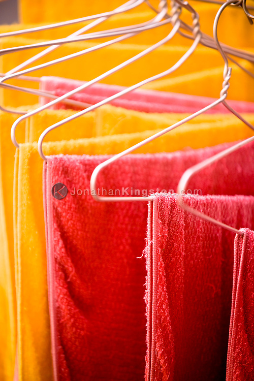 Colorful red and yellow towels hang on clothes hangers, Ho Chi Minh city, Vietnam.