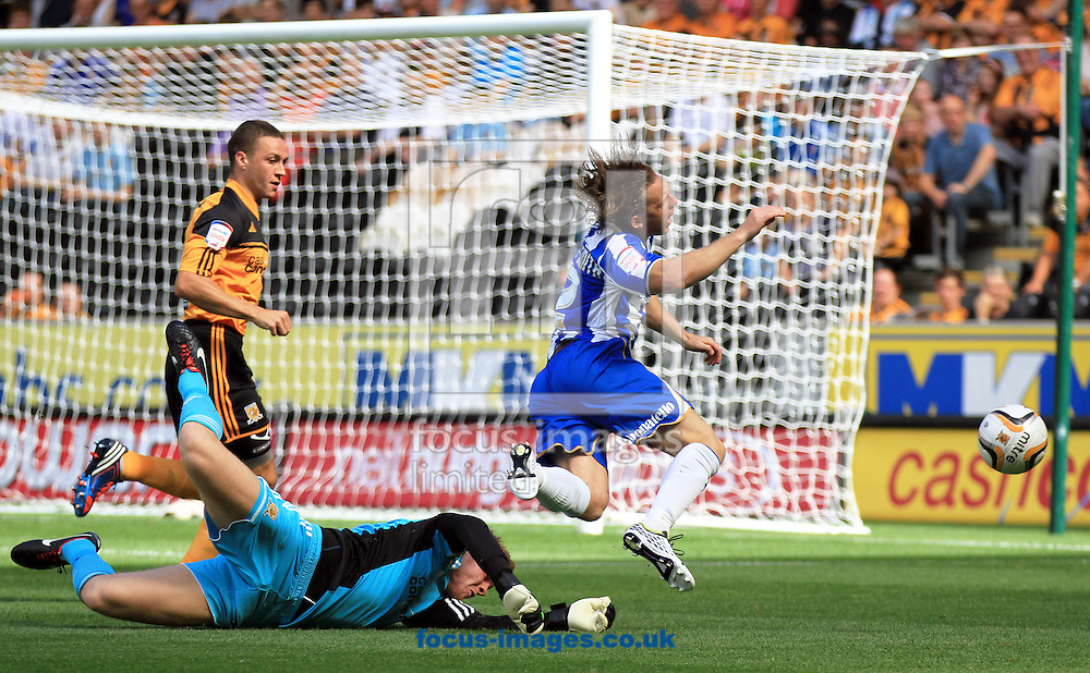 Picture by Richard Gould/Focus Images Ltd +44 7855 403186.18/08/2012.Ben Amos (GK) of Hull City dives for the ball and Craig Mackail-Smith (12) of Brighton and Hove Albion plays for a penalty during the Barclays Premier League match at the KC Stadium, Kingston upon Hull.