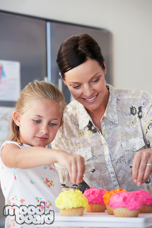 Mother and Daughter Decorating Cupcakes in kitchen