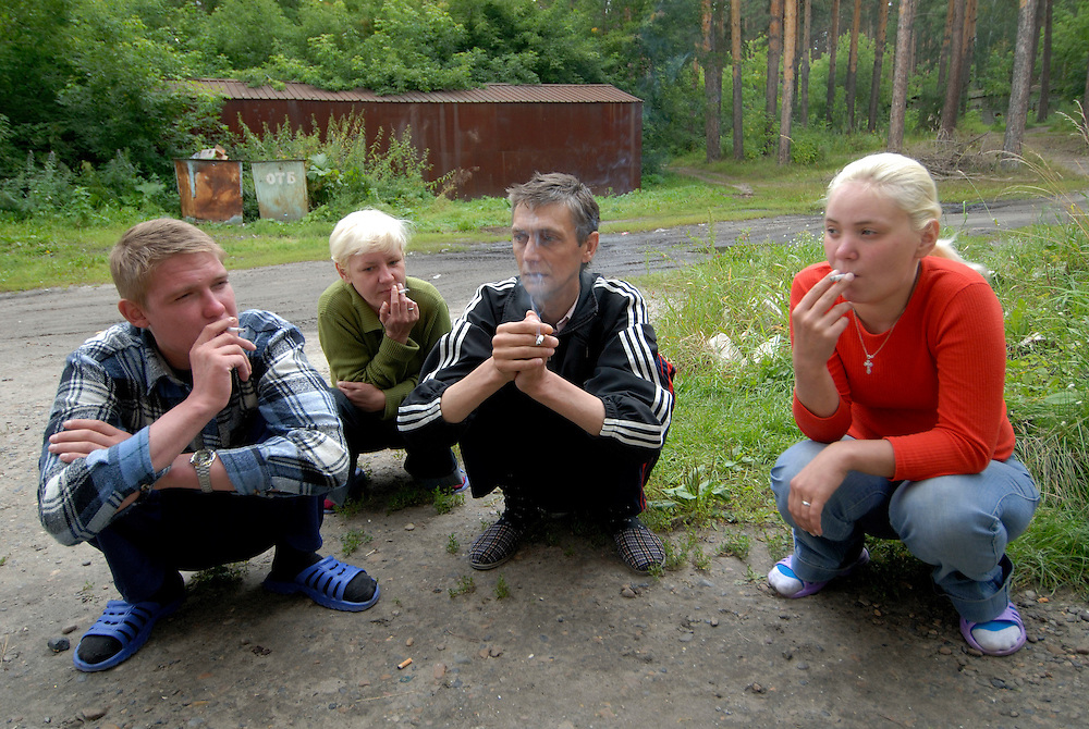 Russia. Tomsk (Siberia). 24.08.2007. TB Hospital. MDR (Multi Drug Resistant) ward. Portraits of TB patients smoking outside the MDR ward. The squatting position is a habit patients pick up in prison; where they have not chairs to sit on.