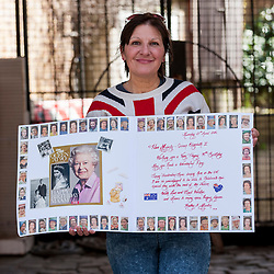© Licensed to London News Pictures. 20/04/2016. Windsor, UK. Kathy Martin, 53, originally from Melbourne, Australia, now Beckenham, Kent, holds up a homemade birthday card and is one of the keen royal fans who will camp out overnight in order to be in prime position in order to see The Queen as she takes part in a walkabout outside Windsor Castle tomorrow her 90th birthday tomorrow. © Stephen Chung / Alamy Live News Photo credit : Stephen Chung/LNP