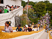 "15 JULY 2011 - PHRA PHUTTHABAT, SARABURI, THAILAND:  People walk up the stairs to Wat Phra Phutthabat in Saraburi province of Thailand, Friday, July 15. Wat Phra Phutthabat in Phra Phutthabat, Saraburi, Thailand, is famous for the way it marks the beginning of Vassa, the three-month annual retreat observed by Theravada monks and nuns. The temple is highly revered in Thailand because it houses a footstep of the Buddha. On the first day of Vassa (or Buddhist Lent) people come to the temple to ""make merit"" and present the monks there with dancing lady ginger flowers, which only bloom in the weeks leading up Vassa. They also present monks with candles and wash their feet. During Vassa, monks and nuns remain inside monasteries and temple grounds, devoting their time to intensive meditation and study. Laypeople support the monastic sangha by bringing food, candles and other offerings to temples. Laypeople also often observe Vassa by giving up something, such as smoking or eating meat. For this reason, westerners sometimes call Vassa the ""Buddhist Lent."" The tradition of Vassa began during the life of the Buddha. Most of the time, the first Buddhist monks who followed the Buddha did not stay in one place, but walked from village to village to teach. They begged for their food and often slept outdoors, sheltered only by trees. But during India's summer rainy season living as homeless ascetics became difficult. So, groups of monks would find a place to stay together until the rain stopped, forming a temporary community. Wealthy laypeople sometimes sheltered monks on their estates. Eventually a few of these patrons built permanent houses for monks, which amounted to an early form of monastery. Photo by Jack Kurtz / ZUMA Press  PHOTO BY JACK KURTZ"