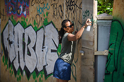 "© Licensed to London News Pictures. 23/08/2019. London, UK. A woman spray paints ""SOS AMAZONIA"" on to boarding protecting residential property as preparations in Notting Hill, West London begin of the 2018 Notting Hill Carnival which starts this weekend. Warm weather is expected over the bank holiday weekend with carnival attracting over 1 million people to the capital. Photo credit: Ben Cawthra/LNP"