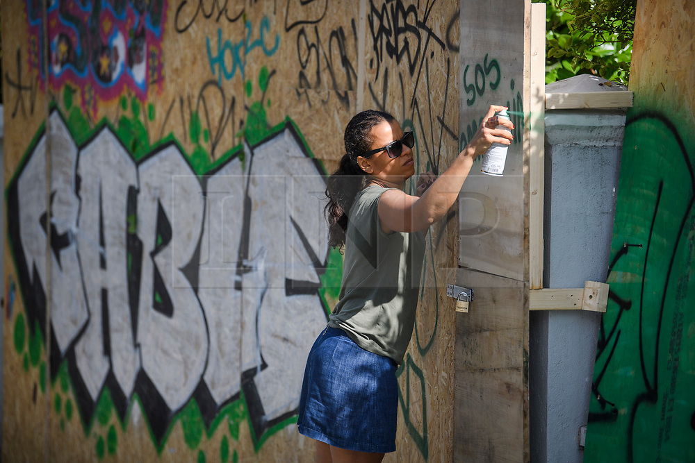 """© Licensed to London News Pictures. 23/08/2019. London, UK. A woman spray paints """"SOS AMAZONIA"""" on to boarding protecting residential property as preparations in Notting Hill, West London begin of the 2018 Notting Hill Carnival which starts this weekend. Warm weather is expected over the bank holiday weekend with carnival attracting over 1 million people to the capital. Photo credit: Ben Cawthra/LNP"""