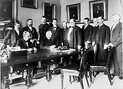 French Ambassador Pierre Paul Cambon signing the Peace Protocol, as President William McKinley and ten other men watch. c1898.