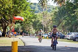 "Children in the 9-11 category race during the bike segment.  ""Run, Bike, Swim"" the Rotary Sunrise Kids Triathalon at Magens Bay.  St. Thomas, USVI.  11 April 2015.  © Aisha-Zakiya Boyd"