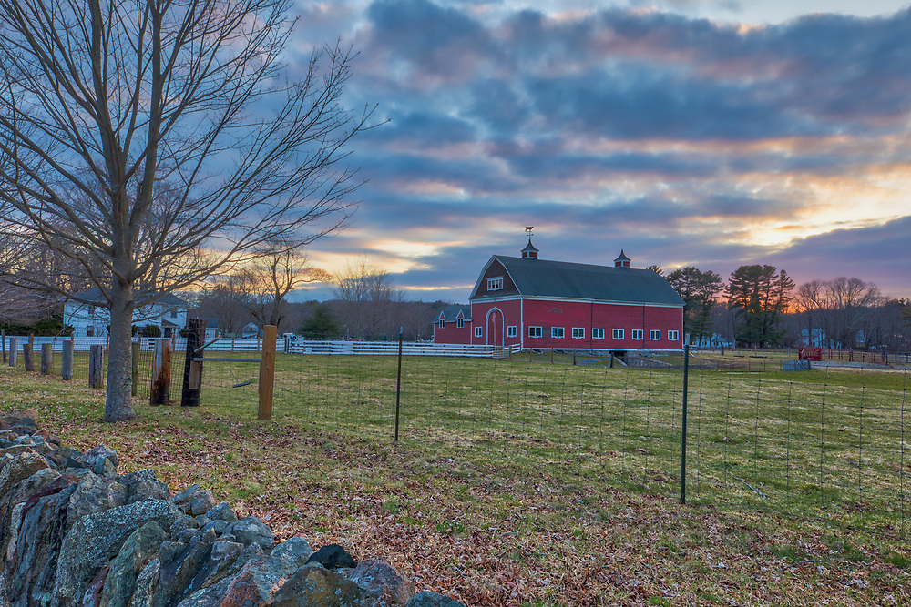 A rustic red barn as clouds catch the sunset color near Natick, MA in rural Massachusetts. Spring rains and colors have not quite moved into New England this year but the red barn, white fence, stone wall and colorful sunset sky made for a great composition and provided a classic setting for this tranquil moment in time. <br /> Red Barn in rural Massachusetts photography images are available as museum quality photography prints, canvas prints, acrylic prints or metal prints. Flower fine art prints may be framed and matted to the individual liking and decorating needs at<br /> <br /> https://juergen-roth.pixels.com/featured/rural-massachusetts-rustic-red-barn-juergen-roth.html<br /> <br /> All New England red barns photographs are available for digital and print use at www.RothGalleries.com. Please contact me direct with any questions or request. <br /> <br /> Good light and happy photo making!<br /> <br /> My best,<br /> <br /> Juergen<br /> Image Licensing: http://www.RothGalleries.com <br /> Fine Art Prints: http://juergen-roth.pixels.com<br /> Photo Blog: http://whereintheworldisjuergen.blogspot.com<br /> Twitter: https://twitter.com/naturefineart<br /> Facebook: https://www.facebook.com/naturefineart <br /> Instagram: https://www.instagram.com/rothgalleries