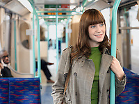 Smiling Young Woman Standing on Commuter Train holding bar