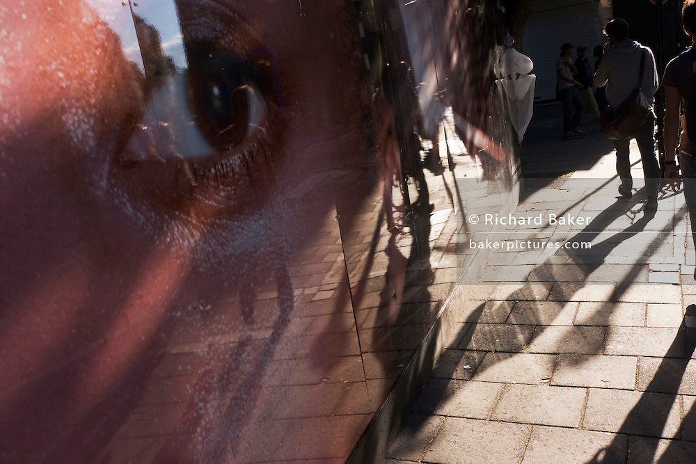 A giant eye from a construction site hoarding watches pedestrians and their long shadows on Neal Street, London.