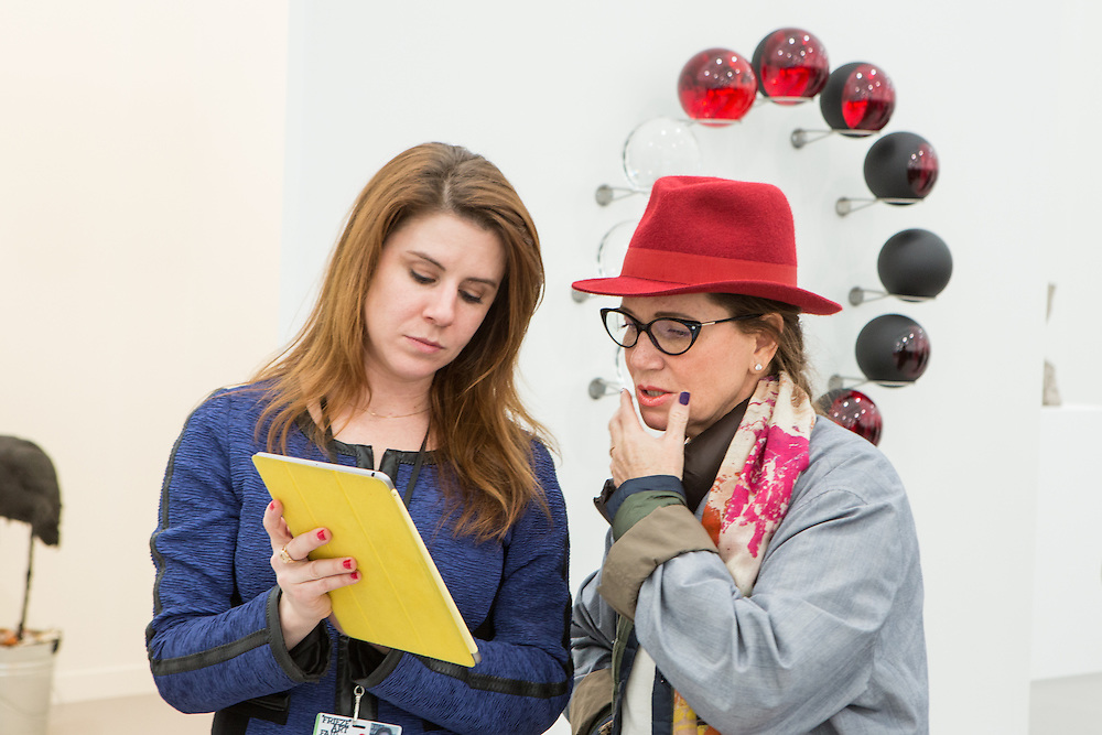 "New York, NY - 6 May 2016. Frieze New York art fair. A woman talks to a gallerist in the Tanya Bonakdar Gallery. Behind them is ""Red life cycle"" by Olafur Eliasson."