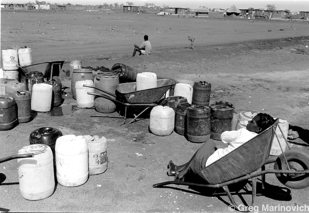 A woman waits for her turn to collect water in the homeland of Gazankulu, northern Transvaal (now Limpopo Province). Thousands of people were suffering from malnutrition in area, may 1992. (Photo by Greg Marinovich)