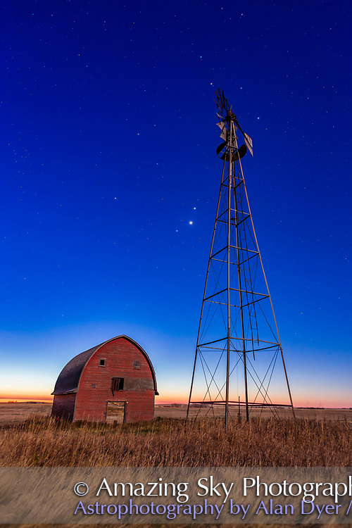 Mars, Venus and Jupiter (in that order from top to bottom) in a triangle, in conjunction, at an old farmstead near Vulcan, Alberta, in the morning twilight, October 28, 2015. Illumination is from the nearly Full Hunter&rsquo;s Moon in the west. The trio of planets were in Leo in a fine conjunction not to be repeated until November 21, 2111. Almost all of Leo is visible here, with Regulus, the constellation&rsquo;s brightest star, just to the right of the windmill blades at top.<br /> <br /> This is a stack of 6 exposures for the ground, mean combined to smooth noise, and one exposure for the sky, all  10 seconds at f/4 and ISO 800 with the Canon 6D and Canon 24mm lens.