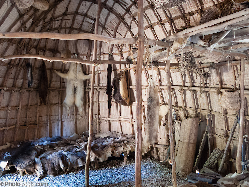 """Reed-covered houses and cultural tools are recreated at Powhatan Indian Village at Jamestown Settlement, Virginia, USA. Animal skins with fur kept people warm. Jamestown, the first permanent English settlement in the Americas, was founded as James Fort in 1607 within an area controlled by the Paspahegh tribe, which was part of the Powhatan Confederacy of tribes, Tsenacommacah, comprised of about 14,000 native people ruled by Wahunsonacock (sometimes called Powhatan). """"Jamestown Settlement"""" is the Commonwealth of Virginia's portion of the historical sites and museums at Jamestown. Created as part of the 350th anniversary celebration in 1957 as Jamestown Festival Park, Jamestown Settlement is adjacent to the complementary """"Historic Jamestowne"""" museum (which is on Jamestown Island, is the actual historic and archaeological site where the first settlers lived, and is run by the National Park Service and Preservation Virginia)."""