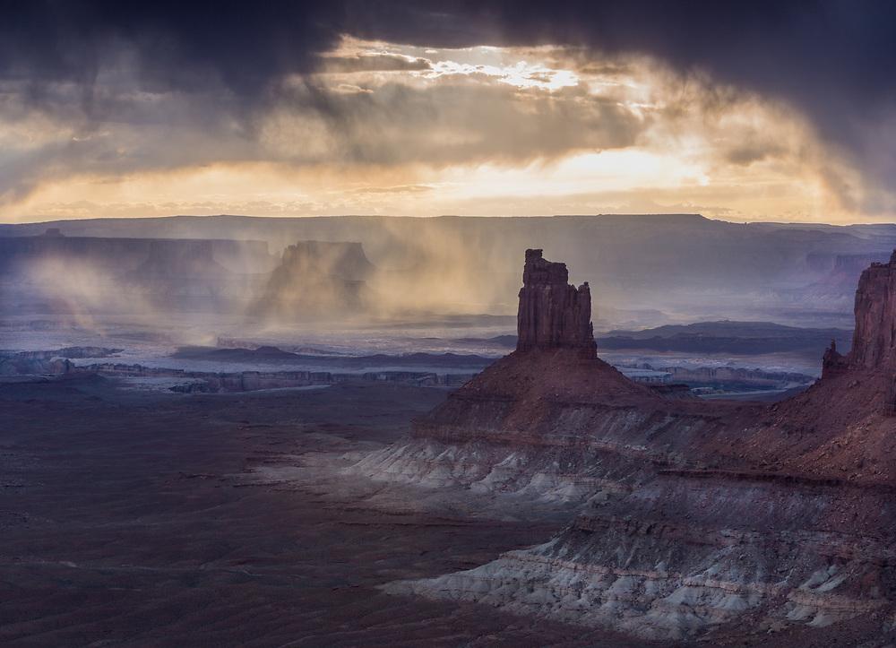 sunset through passing virga rain in Canyonlands National Park, Utah