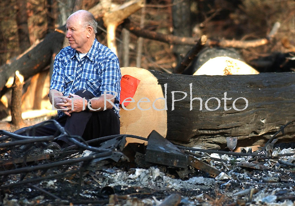 Harold Sponsler looks over whats left of his home as he and other residents return to their homes along Hook Creek Drive in Cedar Glen, Calif. Wednesday, Nov 5th 2003.