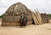 Africa, Ethiopia, Omo valley, a family of the Arbore tribe stands in front off their straw hut