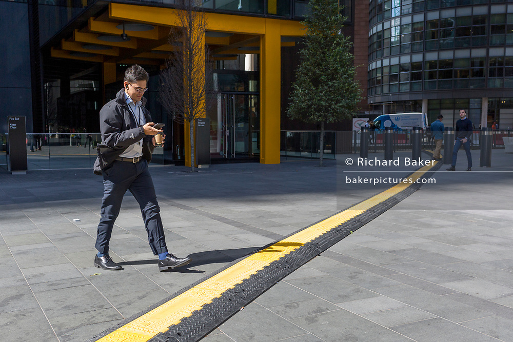 A lunchtime office worker walks and checks messages seemingly unaware of the trip hazard ahead - a yellow line covering hazardous electrical cabling at Leadenhall in the City of London, (aka The Square Mile) the capital's financial district, on 2nd September 2019, in London, England.