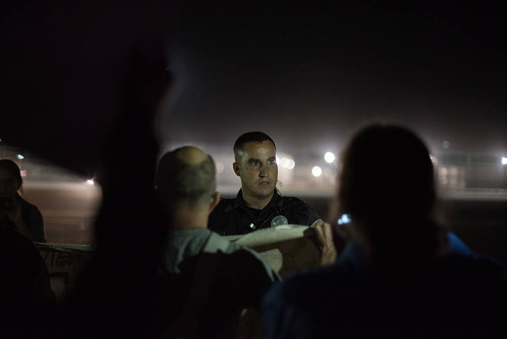 An Eloy police officer orders demonstrators to move back during a vigil held for detained immigrants outside the Eloy Detention Center in Eloy, Arizona on November 10, 2017. This demonstration was part of a weekend of actions called the SOA Watch Border Encuentro held along the Arizona, U.S.-Sonora, Mexico border region focused on immigrant rights, the demilitarization of the border, and other human rights issues.