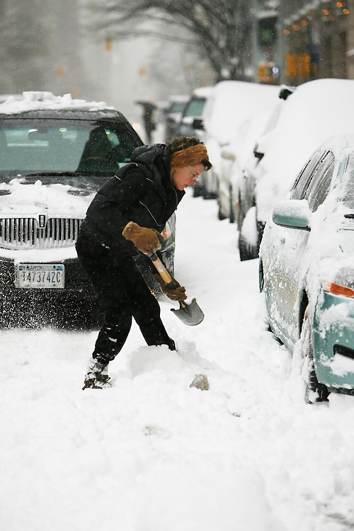 A woman shoveling snow on Madison Ave as the region is hit with a snow storm on February 26, 2009 in New York City. photo by Joe Kohen for The New York Times