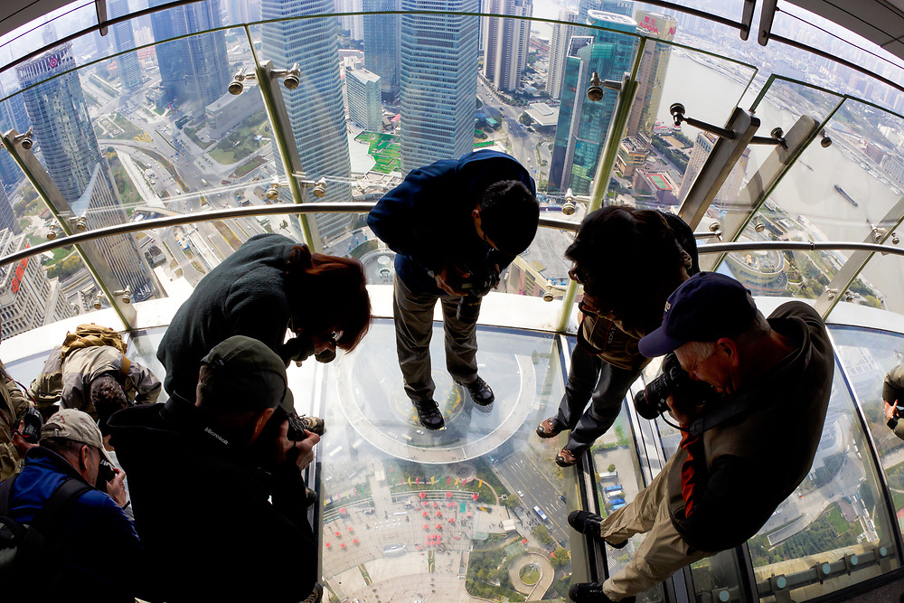Photographers stand on the glass floor of the Pearl Building in Shanghai China.
