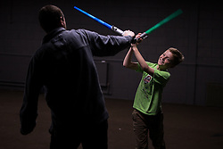 "© Licensed to London News Pictures . 06/12/2015 . Manchester , UK . Father and son Thomas (ten) and Ryan Mitchell (40) (from Cheshire) duel with lightsabers . Fans attend Star Wars exhibition "" For the Love of the Force "" at Bowlers Exhibition Centre in Manchester . Photo credit : Joel Goodman/LNP"