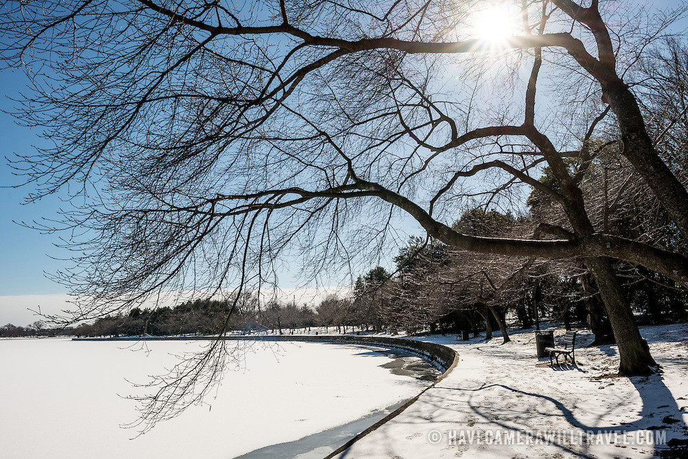 Washington DC's famous cherry trees, devoid of flowers and leaves for the winter, arch over a snow-covered walkway ringing the Tidal Basin. The Tidal Basin in Washington DC is covered by layers of ice and snow. Winter temperatures have been lower than average for the region.