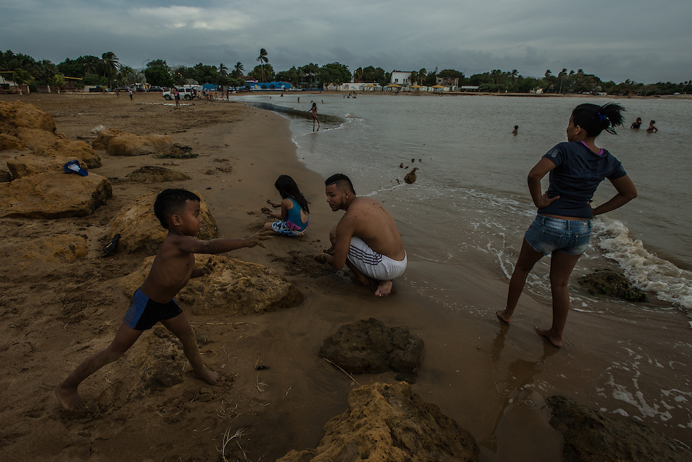 "LA VELA, VENEZUELA - SEPTEMBER 11, 2016:  Roymar Bello plays with her son, husband and niece at the beach, trying to make the most out of her last weekend at home before leaving the country to work undocumented in Aruba. Despite having the largest known oil reserves in the world, Venezuela is suffering from hyperinflation and a severe economic crisis making affordable food difficult for most middle and working class families to access.  Well over 150,000 Venezuelans have fled the country in the last year alone, the highest in more than a decade, according to scholars studying the exodus. As Hugo Chávez's Socialist-inspired revolution collapses into economic ruin, as food and medicine slip further out of reach, the new migrants include the same impoverished people that Venezuela's policies were supposed to help. ""We have seen a great acceleration,"" said Tomás Paez, a professor who studies immigration at the Central University of Venezuela. He says that as many as 200,000 Venezuelans have left in the last year, driven by how much harder it is to get food, work and medicine — not to mention the crime such scarcities have fueled.  PHOTO: Meridith Kohut for The New York Times"