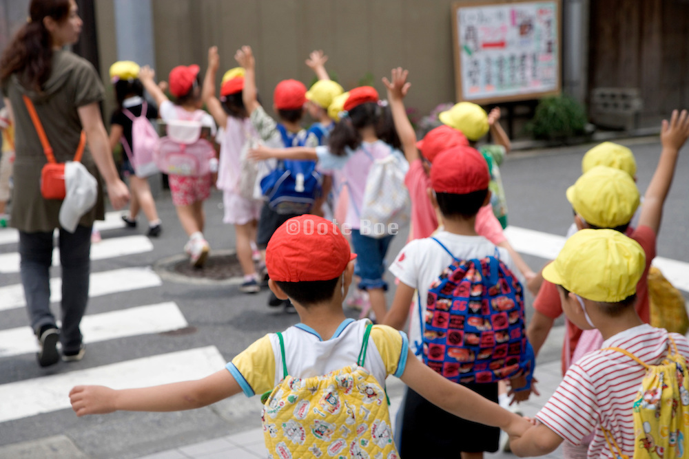 young school children crossing at a pedestrian crossing Japan