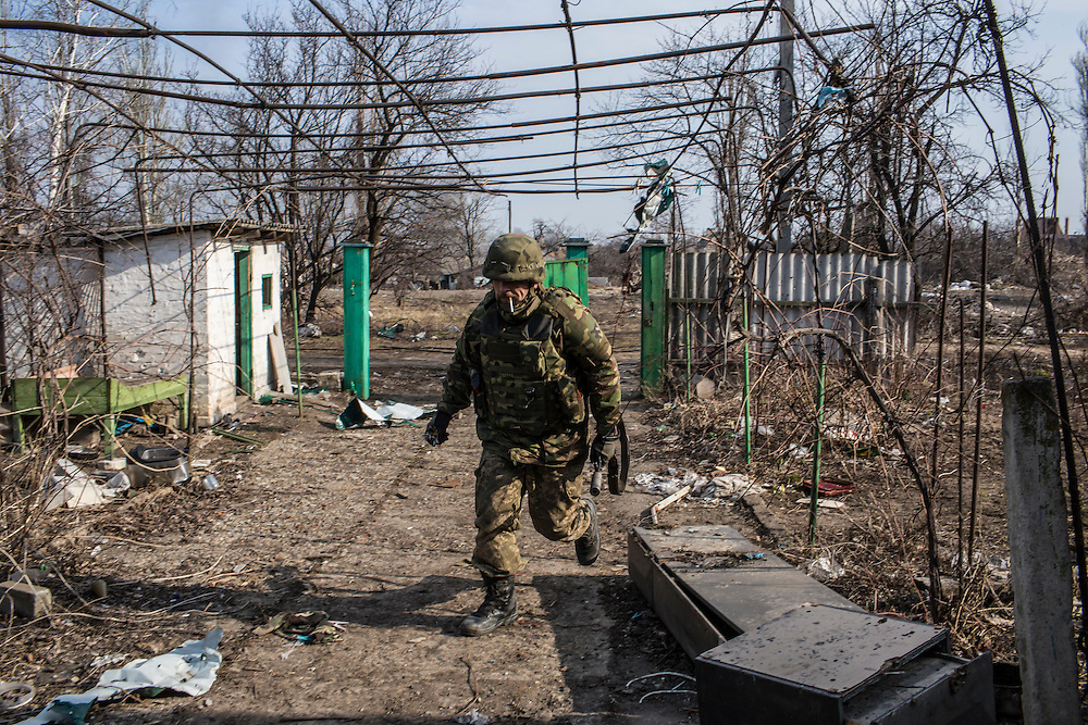 PISKY, UKRAINE - MARCH 20, 2015: Volodya, a fighter for the Dnipro-1 battalion, a pro-Ukrainian militia, runs from a front line trench for cover in the heavily contested town of Pisky, Ukraine. CREDIT: Brendan Hoffman for The New York Times