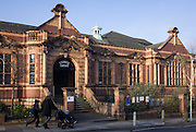 A mother leads her kids past the exterior frontage of Carnegie Library in Herne Hill. Faced with the closure of its local library, Lambeth council plan to close the facility used by the community as part of austerity cuts, saying they will convert the building into a gym and privately-owned gentrified businesses - rather than a much-loved reading and learning resource. £12,600 was donated by the American philanthropist Andrew Carnegie to help build the library which opened in 1906. It is a fine example of Edwardian civic architecture, built with red Flettan bricks and terracotta, listed as Grade II in 1981.
