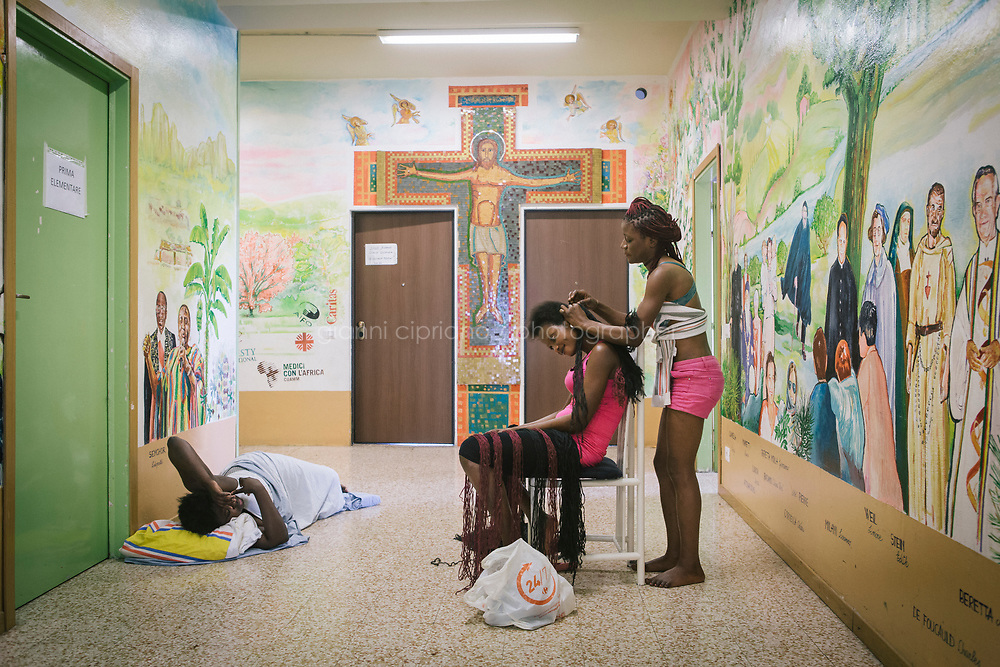 COMO, ITALY - 21 JUNE 2017: Sandra Obodo (center, 26), a Nigerian migrant, is seen here as one friend braids her hair and another sleeps at her foot, in the center ran by priest Giusto della Valle in Como, Italy, on June 21st 2017. Ms. Obodo said she crossed over from Libya nine months ago after escaping retribution murders at home and that a second boat she departed with was lost at sea.<br /> <br /> Residents of Como are worried that funds redirected to migrants deprived the town&rsquo;s handicapped of services and complained that any protest prompted accusations of racism.<br /> <br /> Throughout Italy, run-off mayoral elections on Sunday will be considered bellwethers for upcoming national elections and immigration has again emerged as a burning issue.<br /> <br /> Italy has registered more than 70,000 migrants this year, 27 percent more than it did by this time in 2016, when a record 181,000 migrants arrived. Waves of migrants continue to make the perilous, and often fatal, crossing to southern Italy from Africa, South Asia and the Middle East, seeing Italy as the gateway to Europe.<br /> <br /> While migrants spoke of their appreciation of Italy&rsquo;s humanitarian efforts to save them from the Mediterranean Sea, they also expressed exhaustion with the country&rsquo;s intricate web of permits and papers and European rules that required them to stay in the country that first documented them.