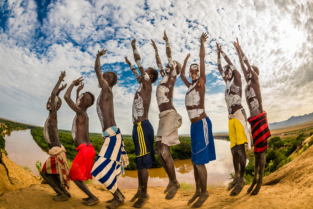 Kara tribe boys with body chalk paintings on their bodies jump in the air, with the Omo River behind. Dus village, Omo Valley, Ethiopia. Omo Valley, Ethiopia.