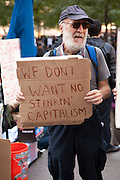 "A bearded man carries  a sign reading ""We don't want no stinkin' capitalism"""