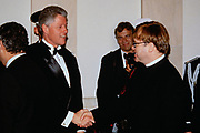 U.S. President Bill Clinton, left, shakes hands with Musician Elton John in the receiving line at the State Dinner at the White House February 5, 1998 in Washington, DC.