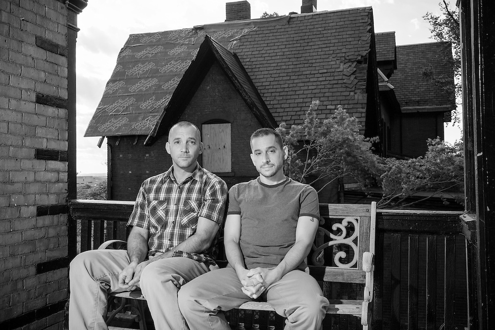 Don Courtemanche & Bryce Tolassi same sex married couple seated on bench on porch with tornado damaged house behind them