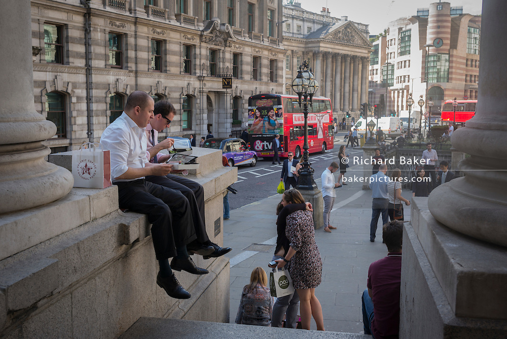Lunchtime City workers eat lunches beneath the pillars of Royal Exchange on 13th September 2016, in the City of London, England.