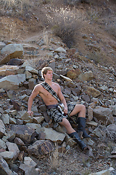 sexy good looking man in a kilt outdoors