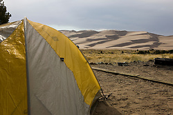 A tent in the Pinyon Flats campground overlooks the dune field.  Great Sand Dunes National Park and Preserve contains the tallest sand dunes in North America. The Dunefield, topping off with Star Dune at 750 feet, is created by sand trapped by the nearby Sangre de Christo Mountains (larger rougher grains and pebbles) and the San Juan Mountains (65 miles to the west).  Waterways such as Medano Creek help carry the sediment down to the San Luis valley where the dunes are found. Great Sand Dunes National Park and Preserve, Mosca, Colorado.