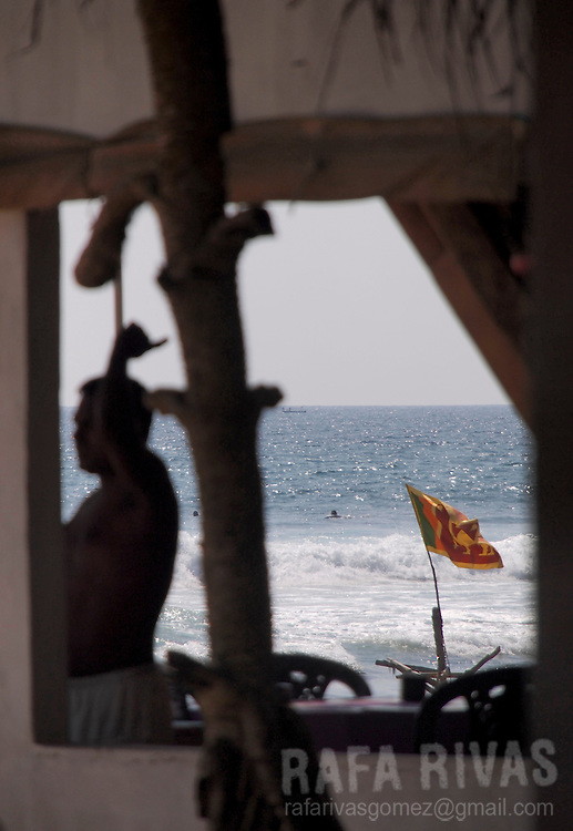 A man stands next to window as a Sri Lankan flag waves at the Hikkaduwa beach, In Sri Lanka, on February 24, 2011