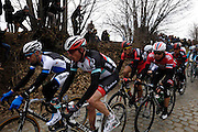 Belgium, March 31 2013: Maarten Wijnants, BLANCO PRO CYCLING TEAM, and Gregory Rast, RADIOSHACK-LEOPARD, lead Edvald Boasson Hagen, SKY PROCYCLING, and other riders up the Oude-Kwaremont for the final time during the Ronde van Vlaandaren 2013 cycle race. Copyright 2013 Peter Horrell.